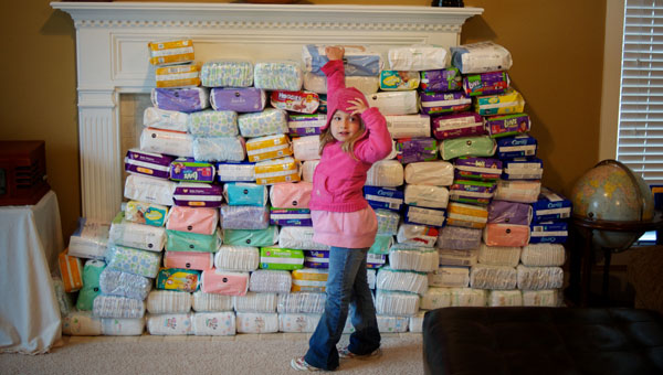 Emily Brannon shows the stack of diapers she collected for Save-A-Life to a group of visitors at her house in Maylene. (Reporter Photo/Jon Goering)