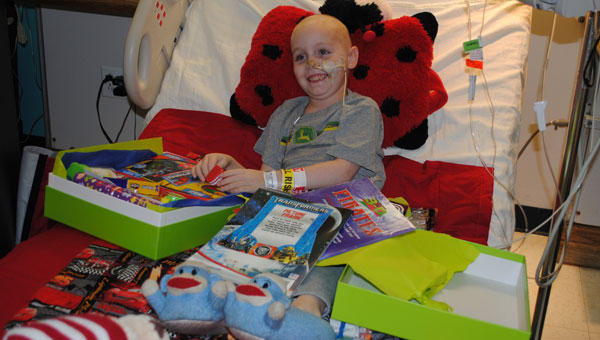 Tristian Lane Jones opens a Cheeriodical from his hospital bed at Children's of Alabama. (Contributed)