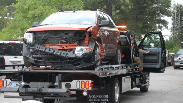 A wrecker transports Richard Philpot's heavily damaged Ford Edge after police said the suspect allegedly tried to use the vehicle to run over two Helena police officers in 2012. (File)