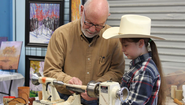 Dave Chanslor teaches Bella Fancher how to turn wood to make a honey dipper at Montevallo's Arbor Day Feb. 23. (Reporter photo/Christine Boatwright)