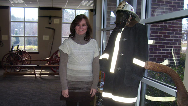 Lori King, who has been involved with the Chelsea Fire Department for most of her life and still works with them at City Hall, poses with early Chelsea Fire Department gear displayed in the city's Historical Museum. (contributed)