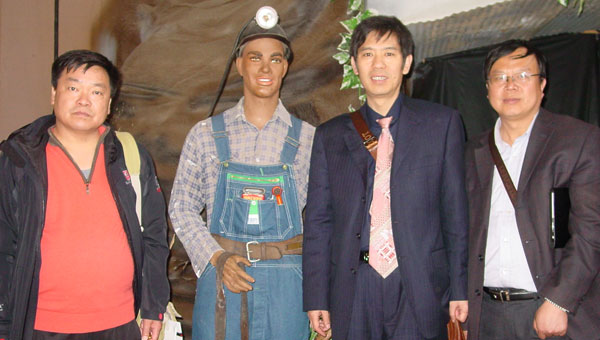 """Visiting Chinese coal mine operators pose with """"Sam,"""" who stands at the opening to the simulated coal mine at Aldrich Museum. (Contributed)"""