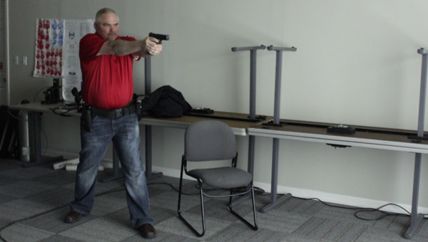 Calera Councilman Chris Bunn trains with a shooting simulation at the Calera Police Department Feb. 26. (Reporter photo/Christine Boatwright)