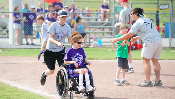 Ellie Meeks hurries to first base with the help of her buddy, Wesley Posey. (Reporter photo/Jon Goering)