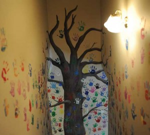 Child abuse victims and sometimes their family members leave handprints on a mural of a tree downstairs when they complete their time at Owens House — a sign to future visitors that others have walked in their shoes. ABOVE LEFT: Art created by victims and counselors hangs on the walls throughout Owens House. (Photo by Jon Goering.)