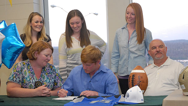 PHS senior Eli Beall, center, is surrounded by his mother, Becky, father, Larry, and sisters, Taylor, Chelsea and Meaghan during a March 15 signing with Faulkner University in the school's cafeteria. (Reporter Photo/Neal Wagner)