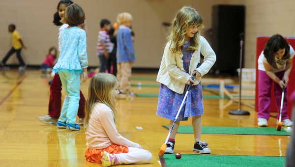 Hanna Reamer and Clea Collins, Riverchase Elementary School kindergarteners, work on their putting skills during the school's golf unit on March 11. (Reporter Photo/Jon Goering)