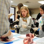 Riverchase third-graders Anabelle Kunz and Maddie Ellis react as UAB students show them the parts of a pig's heart during PhUn week on March 20. (Reporter Photo/Jon Goering)