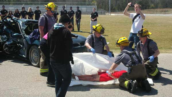 "Emergency response personnel wrap a ""victim"" in a body bag during ""Every Fifteen Minutes,"" a simulation several Chelsea groups put on to illustrate the negative effects of drunk driving. (Photo by Linda Long.)"