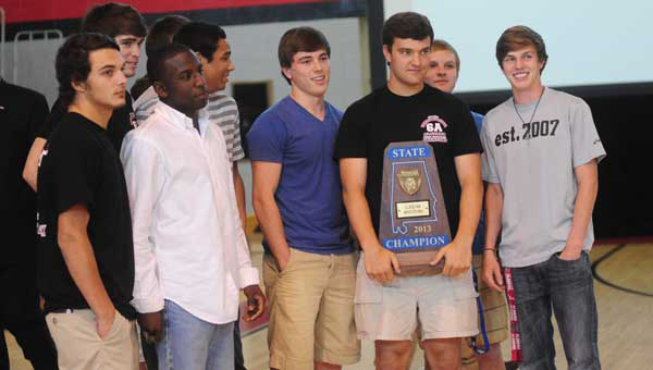 Senior members of the Thompson wrestling team stand for pictures with their 2013 AHSAA Class 6A State Championship trophy during an assembly on April 26. (Reporter Photo/Jon Goering)