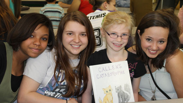 Pelham High School students Aja Bell, left, Lora Kral, second from left, Valley Elementary School first-grader Kathryn and PHS student Haley Giffin, right, at VES during the Children's Book Project day. (Contributed)