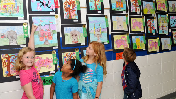 Second graders from Mrs. Sellers' class admire the artwork lining the halls during the annual art show. From left, Riley Hollabaugh (who favors pink), Cadence Williams, Addison Hines and Jacob Stevenson. (contributed)