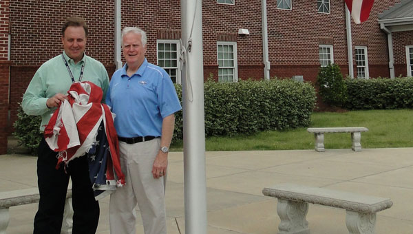 Calera High School Principal Richard Bishop, left, and custodian Robert Moore replaced the school's storm-damaged flag with the flag that draped Bishop's Uncle Luke Huey's casket. (contributed)