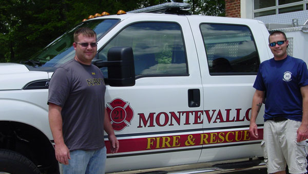 Rescue workers Wesley Lash and Rickey Pennington pose with the Montevallo Fire Department's new truck.  (contributed)