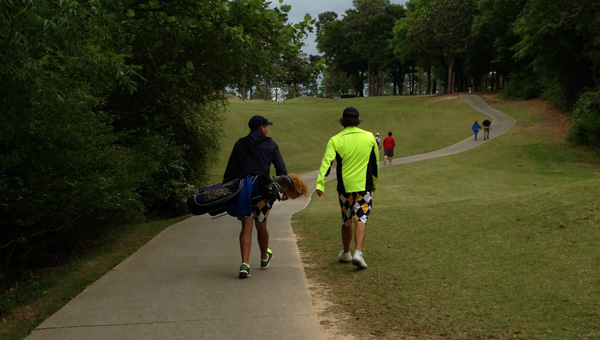Briarwood golfer John Hayden (left) carries teammate Trevor Page's clubs after Page won a close playoff to clinch a spot in the AHSAA 5A State Tournament. (Contributed)