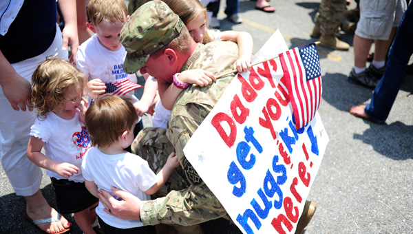 Chris Henderson, a soldier with the Bravo Company 1/167th Infantry Battalion of the Alabama National Guard greets his family, Ashley, Baileigh, James, Michael and Madison on May 20 after a nine-month deployment. (Reporter Photo/Jon Goering)