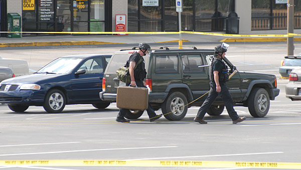 Members of the Hoover Police Department bomb squad carry a suitcase off the scene near Pelham's Big Lots store after an off-duty police officer reported the suspicious package on May 28. (Reporter Photo/Neal Wagner)