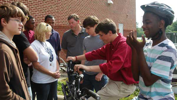 Valinda Pate, Shelby County Board of Education adaptive P.E. teacher, gets some tips from Brian Copes, Calera High School Engineering teacher (center) and his students on how to disassemble a new tandem bicycle for easy transport. (Photo by Linda Long/For the Reporter.)