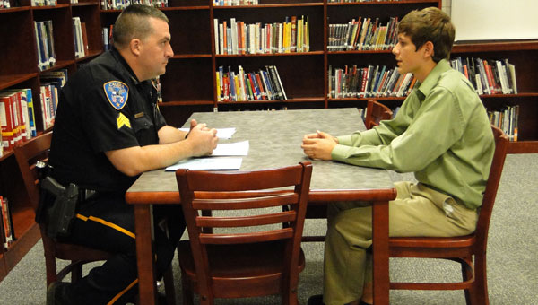 Calera Police Sergeant Deven Heathcock talks with sophomore Zachary Goodwin in a mock interview at Calera High School. (contributed)