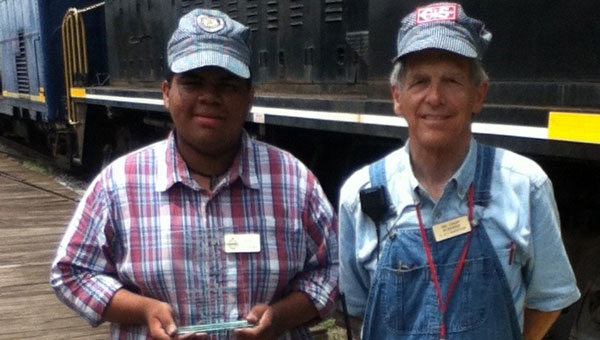 Bailey Reynolds, left, a car host and assistant engineer at the Heart of Dixie Railroad museum, holds the plaque awarded to him for his service as a student volunteer. Standing with him, beside a train on the museum yard, is Neil Smart, main engineer at the museum. (contributed)