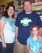 Six-year-old Elizabeth Hyde enjoys a visit to the Chelsea library with her mom and dad Heather and Daryl Hyde. The Hydes also have a daughter Sarah, age 11. (contributed)