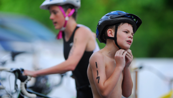 A racer buckles his helmet in transition from swim to bike at the Alabama Sports Festival Youth Traithlon held at Oak Mountain State Park June 23.