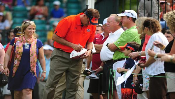 Auburn coach Gus Malzahn signs an autograph for a young fan at the NRC Pro-Am at Shoal Creek June 5.