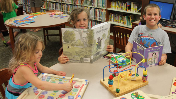 From left, Katie Traywick, 4, McKenna Traywick, 7, and Caleb Traywick, 9, enjoy summer at the Pelham Public Library. (Contributed)
