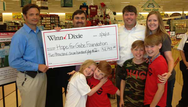 Winn-Dixie Store no. 569 Director Mark Hamilton, Winn-Dixie District Director for Birmingham East, Richard McGough present a check to the Griffin family for the Hope for Gabe Foundation. (Contributed photo.)