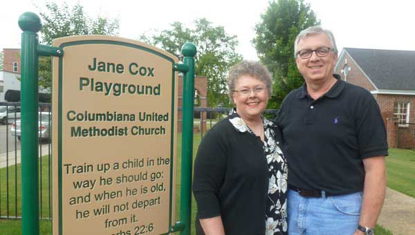 New senior minister Buster Timmons and wife Debbie at the new children's playground at Columbiana United Methodist Church, which was named in memory of the late Jane Cox, KIMCO youth founder and youth leader at CUMC. (Photo by Phoebe Donald Robinson.)