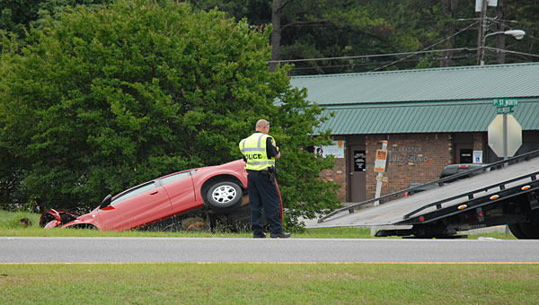 Police close one lane of U.S. 31 on June 6 while a wrecker prepares to remove a red Saturn from a ditch near the Shelby Motor Lodge. (Reporter Photo/Neal Wagner)