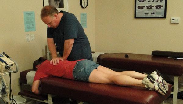 Dr. Jeff Parker makes an adjustment on patient Margaret Danzer. (contributed)