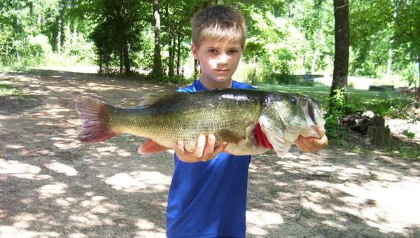 """Ten-year-old Tyler Hardin shows off the 8 pound, 1 ounce bass he caught in a neighbor's lake, before he and his """"Paw Paw"""" Larry Nivens take it to be mounted. (Contributed)"""