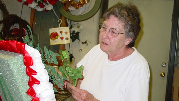 Elizabeth Studdard works on a funeral arrangement in her shop on Island Street. (contributed)