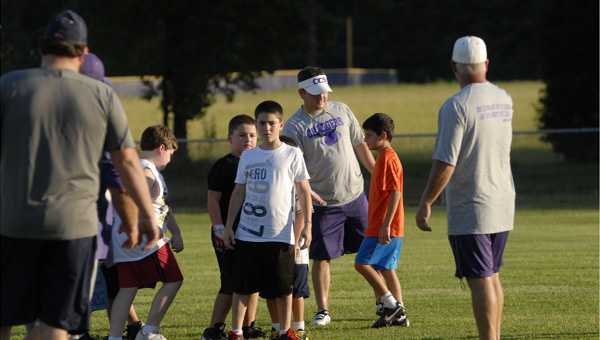 Members of the Cornerstone Christian coaching staff work with young players during a youth football camp on July 25.