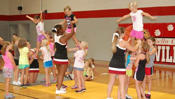 At the Shelby County High School annual cheer camp, kids ages 4 to sixth grade learn how to cheer, dance, chant and stunt with the Shelby County cheerleaders. Here, campers practice stunting. (Reporter Photo/Stephanie Brumfield)