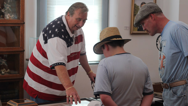 Frank Banks shows off some of his collection to visitors at Columbiana's Liberty Day in June. (Photo by Tyler Essary/For the Reporter.)