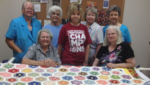 Members of The Lydia Group, from left, are Gloria Tibbs, Catherine Walker, Faylenn McColeman, Carolyn Humber, Eva Taylor, Sharon Bull and Lynne Crocker. The ladies pose with the completed Grandmother's Flower Garden quilt. (contributed)