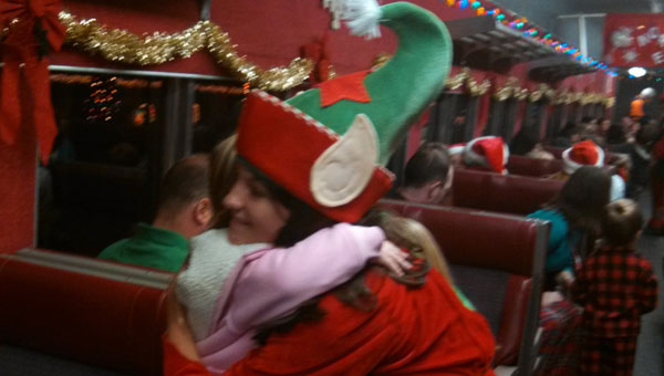 One of Santa's elves gets a hug from a passenger on the North Pole Express. (contributed)