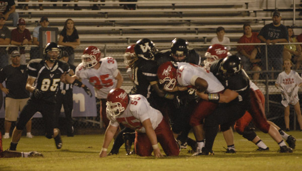 Rodney Groce (31) and a host of Yellow Jackets take down West Blocton's Jaylon Gaines in a 26-20 win Aug. 30