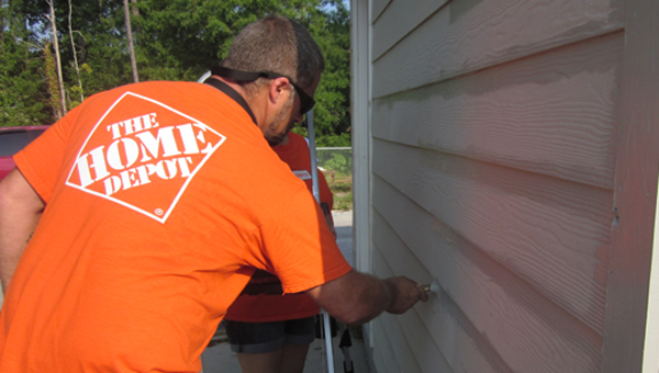 Home Deport employee James Davis paints the Shelby Humane Society's new storage facility as part of a group of volunteers. (Reporter Photo/Stephanie Brumfield)