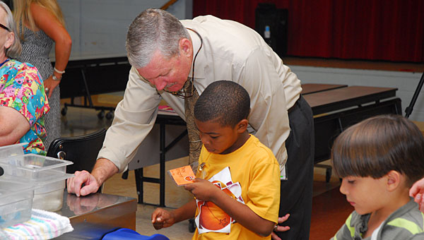 Pelham Mayor Gary Waters helps Valley Elementary School kindergartener Trey Knight punch in his lunch number at the school on Aug. 21. (Reporter Photo/Neal Wagner)