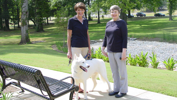 "Co-chairs of the steering committee for the new Library Learning Enrichment Garden, Michele Pawlik and Libbie Rodgers along with ""Cody"" (Michele's walking buddy), look over the beautiful garden. (contributed)"