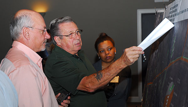 From left, James Brown, Kenneth Foss and Tameka Hughes look over a map of a proposed sidewalk project along Bearden Road during a Sept. 24 ALDOT public meeting. (Reporter Photo/Neal Wagner)