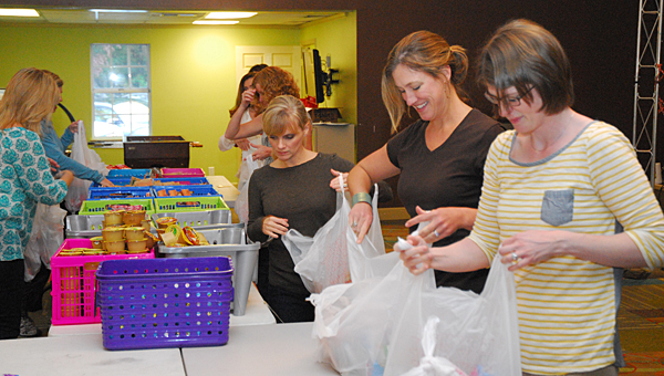 Volunteers with the Junior League of Birmingham work to pack 160 bags to deliver to schools in Alabaster and Montevallo on Oct. 29. (Reporter Photo/Neal Wagner)