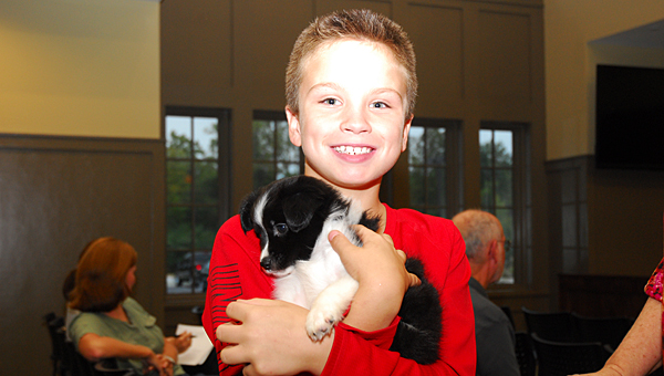 Meadow View Elementary School student Jaxon Bearden holds Alabaster City Schools' newest employee, Warrior, during an Oct. 16 school board meeting at the new Alabaster City Hall. (Reporter Photo/Neal Wagner)