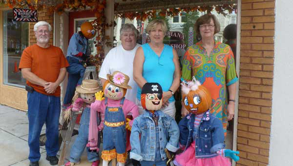 Columbiana Merchants and Professional Association President Andrew Moore (Columbiana Inn), CMPA Vice President Susan Conn (Main Street Florist), Leigh Ann Langley, creator of the Pumpkin Patch Kids, and CMPA Board Member Linda Cook (Busy Hands) in front of Langley's Columbiana Barber Shop decorated with Pumpkin Patch Kids. (Photo by Phoebe Donald Robinson.)