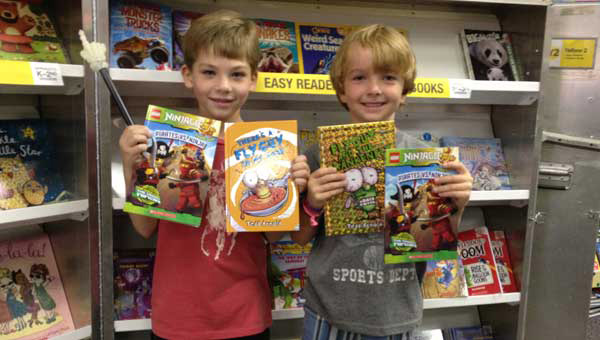 Talan Smith and Weston Brock show off their purchases at the Greystone Elementary book fair. (Photo by Katie McDowell.)