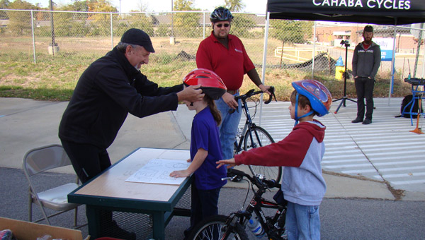 A volunteer helps a rider try on a new helmet at the Greystone YMCA Bike Rodeo Nov. 9. (Contributed)