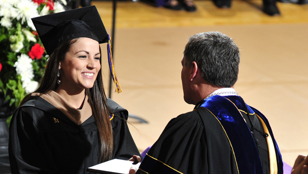 Kelly Triplett Benton receives her diploma, and congratulations, from Dr. John W. Stewart III, University of Montevallo president. (Contributed/Matthew Orton)